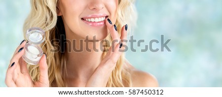 Beautiful smiling girl with wavy hair cares of her lips.  Young blonde woman applying make-up cosmetic SPA product. Model using lip balm or gloss for hydration, nutrition, smoothing.