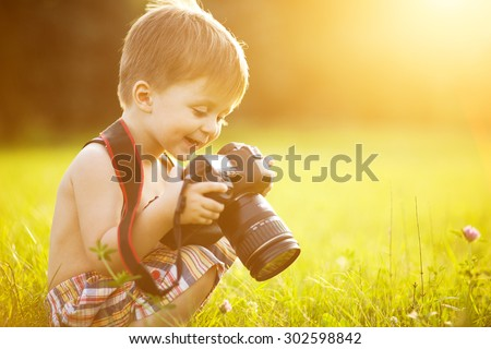 Beautiful smiling kid boy holding a DSLR camera in park - stock photo