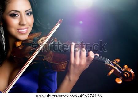 Beautiful smiling latin woman playing violin - stock photo