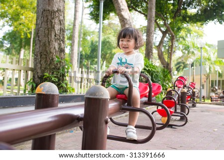beautiful smiling little asian girl on outdoor playground equipment - stock photo