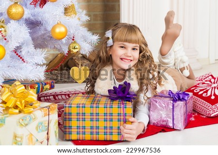beautiful  smiling  little blonde girl near the christmas tree with gifts dressed fur vest and knitted socks - stock photo