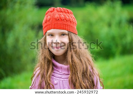 Beautiful smiling little girl in red beret closeup on background of city park. - stock photo
