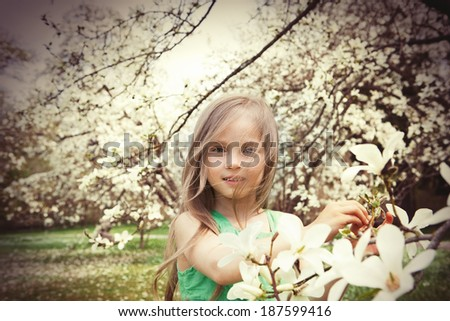 Beautiful smiling little girl in the spring garden - stock photo