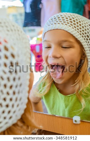 Beautiful smiling little girl looks in the mirror and shows tongue. - stock photo