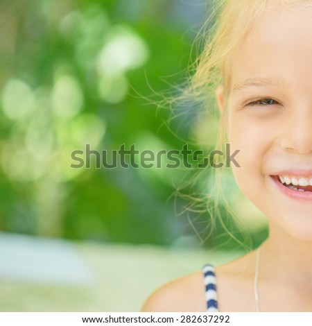 Beautiful smiling little girl, on gray background. - stock photo