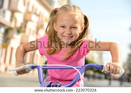 Beautiful smiling little girl riding a bike on the street in city - stock photo