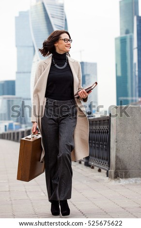 beautiful smiling middle-aged woman in a bright coat goes with a wooden case and books in hand along the waterfront on the background the skyscrapers of the business district of the city