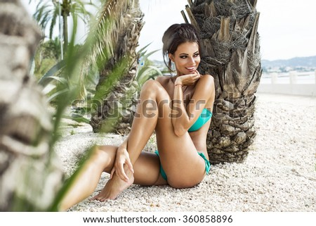 Beautiful smiling model under the palm in summer scenery - stock photo
