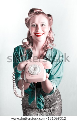 Beautiful Smiling Pinup Woman Holding Retro Turn Dial Phone In A Contact Us Concept - stock photo