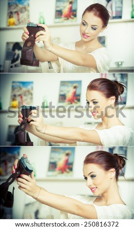 Beautiful, smiling red hair woman taking photos of herself with a camera. Fashionable attractive female taking a self portrait. Selfie, indoor, horizontal. Beautiful redhead taking pictures of herself - stock photo