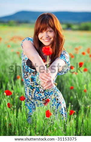 Beautiful smiling teenage girl giving flower to you - stock photo