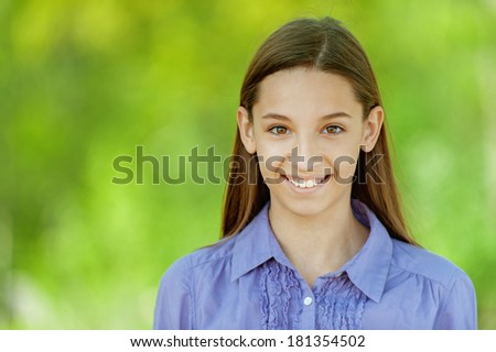 Beautiful smiling teenage girl in blue shirt, against background of summer green park.