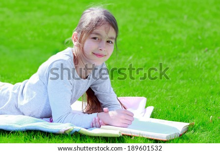Beautiful smiling teenage girl  lying on grass and read book in summer park. - stock photo