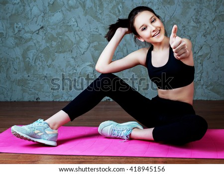 beautiful smiling teenage girl wearing sports clothes with a yoga mat and with her thumb up - stock photo