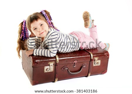 beautiful smiling toddler girl laying on retro suitcase - stock photo