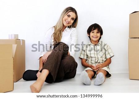Beautiful smiling woman and little boy sitting alogside cardboard box - stock photo
