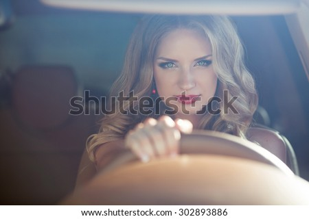 Beautiful Smiling woman driving car, attractive girl sitting in automobile, outdoors summer portrait. - stock photo