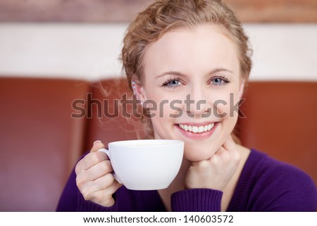 beautiful smiling woman enjoying cup of coffee in coffee shop - stock photo