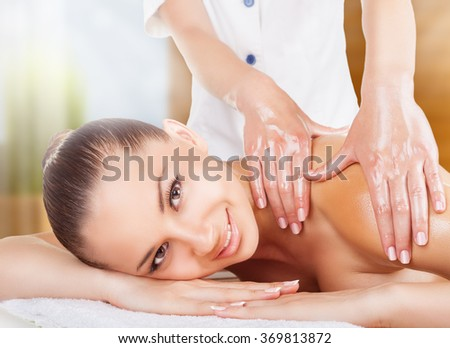 Beautiful smiling woman getting a oil massage in the spa salon - stock photo