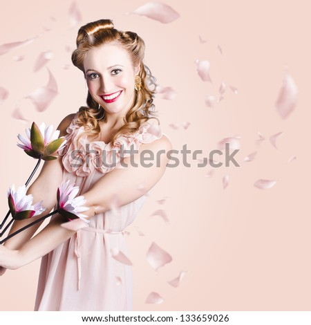 Beautiful smiling woman holding a bunch of lilies dancing in fall of raining flower petals - stock photo