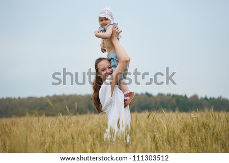 Beautiful smiling woman holds child in the wheat field - stock photo