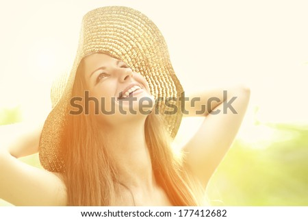 beautiful smiling woman in a hat in the summer sun - stock photo