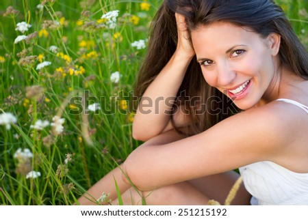 Beautiful smiling woman in flowers - stock photo