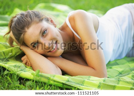 Beautiful smiling woman laying on the grass