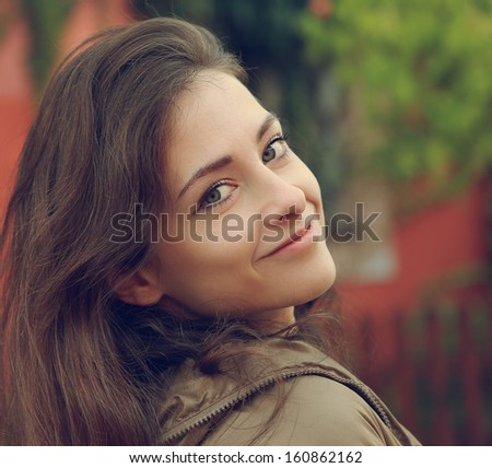 Beautiful smiling woman looking outdoors background. CLoseup portrait - stock photo