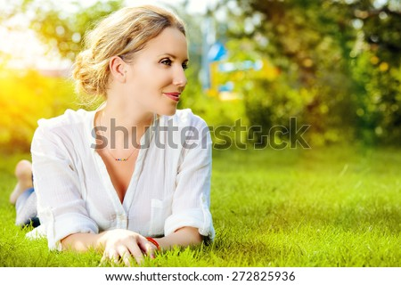 Beautiful smiling woman lying on a grass outdoor. She is absolutely happy.  - stock photo