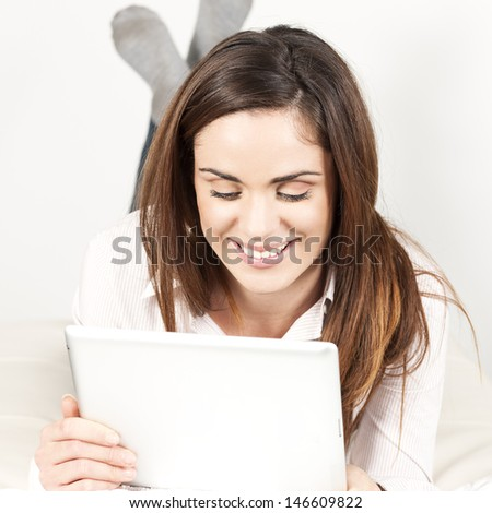 Beautiful smiling woman on sofa with tablet  - stock photo