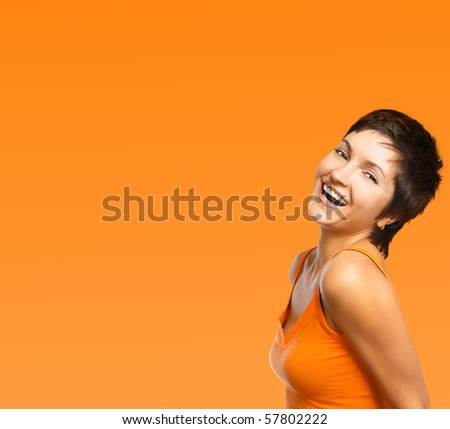 Beautiful smiling woman. Over orange background - stock photo