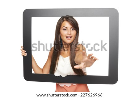 Beautiful smiling woman peeping through tablet frame and stretching her hand attempting to grab something, over white background - stock photo
