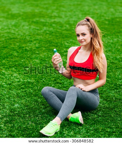 Beautiful Smiling Woman Relaxing on the Grass in the Park During Training. Sport and Fitness Concept - stock photo