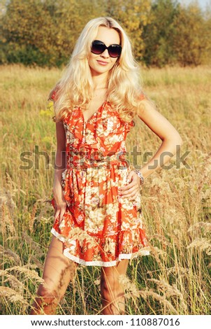 Beautiful smiling woman standing on the field - stock photo