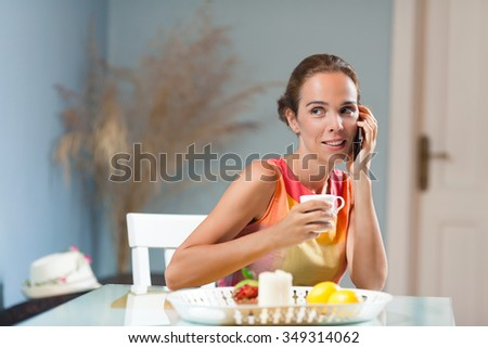 Beautiful smiling woman talking on the phone while enjoying cup of coffee - stock photo