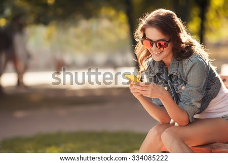 Beautiful smiling woman typing on the smart phone in a park with a green unfocused background - stock photo
