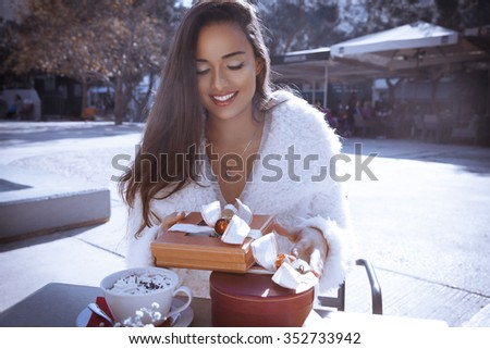 beautiful smiling woman wear white expensive fur coat, drinking coffee and open her gifts. Fashion and holidays style. Valentines day. Outdoor shoot, horizontal - stock photo