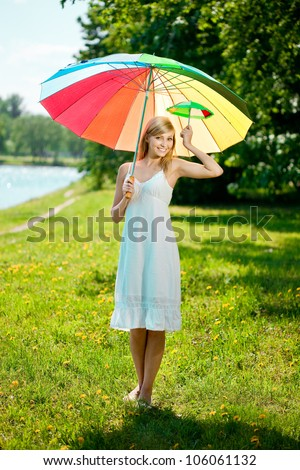 Beautiful smiling woman with a rainbow umbrella outdoors