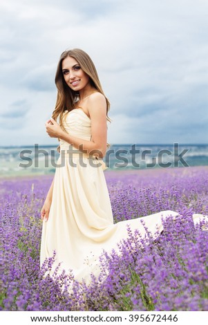 Beautiful smiling woman with flying hair is wearing nice white dress at field of purple lavender flowers