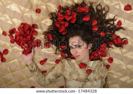 Beautiful smiling woman with red rose petals - stock photo