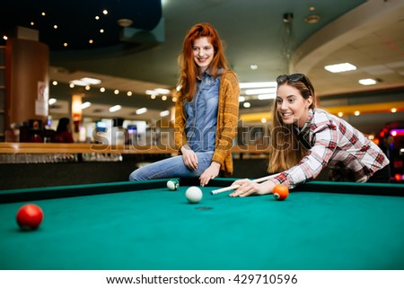 Beautiful smiling women playing billiards at a bar - stock photo