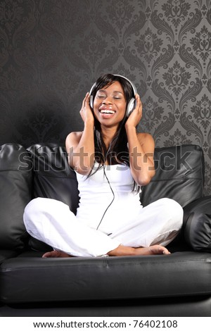Beautiful smiling young african american woman sitting on black leather sofa at home, headphones on listening to music. - stock photo