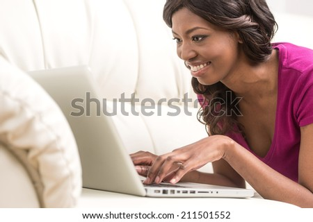 Beautiful smiling young african woman lying on leather sofa at home. happy girl surfing internet with her laptop computer and smiling