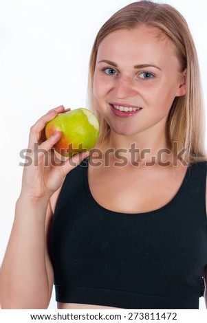 Beautiful smiling young blonde woman with an apple in his hand. A young athletic woman holding a big green apple in her hand - stock photo