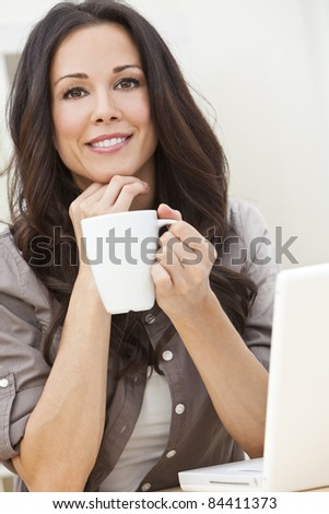 Beautiful, smiling, young brunette woman at home at a table using her laptop computer and drinking a mug of tea or coffee