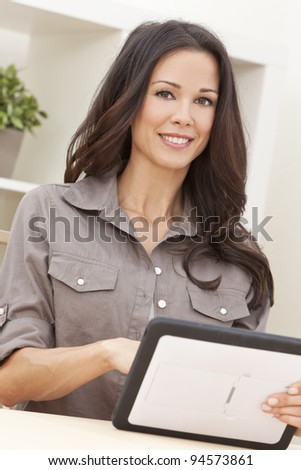 Beautiful, smiling, young brunette woman at home at a table using her tablet computer - stock photo