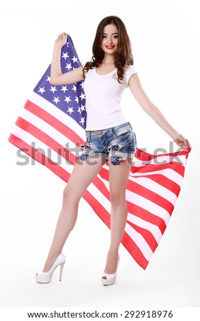 Beautiful, smiling, young brunette woman in style cloth posing with national usa flag in background. 4th july concept. - stock photo