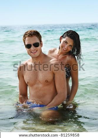 Beautiful smiling young couple having fun in the sea - stock photo