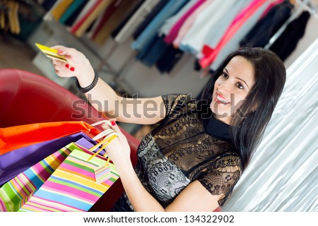 Beautiful smiling young girl shopping with credit card - stock photo